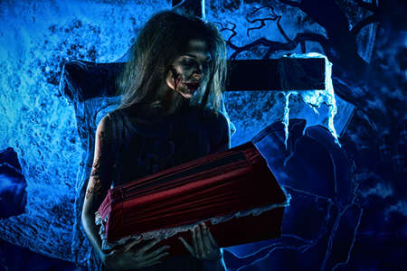 bloodthirsty: Bloodthirsty witch standing at the night cemetery and holding a coffin. Stock Photo