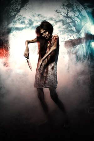 terrific: Bloodthirsty zombi with a knife standing at the night cemetery in the mist and moonlight.