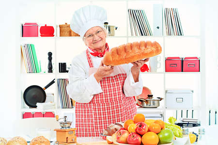 Senior woman chef cooks in the kitchen. photo