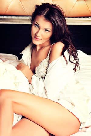 niñas en ropa interior: Feliz mujer joven hermosa en una cama en su casa. Foto de archivo