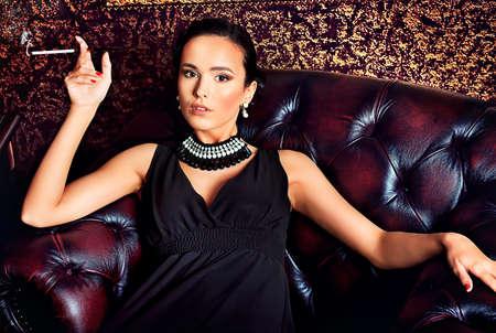 chica fumando: Joven y bella mujer en un interior clásico de lujo.