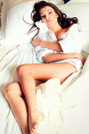 sexy woman on bed: Happy beautiful young woman lying in a bed at home. Stock Photo