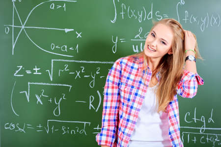 Pretty student girl standing at the blackboard in the classroom. Stock Photo - 18843280