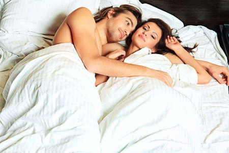 couple au lit: Jeune femme et un homme amoureux couché dans un lit. Banque d'images