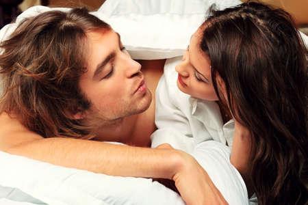 pareja en la cama: Mujer joven y un hombre enamorado acostado en una cama.