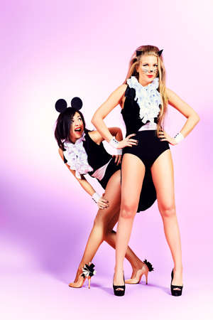 Two sexy playgirls in costumes of cat and a mouse alluring over pink background. photo
