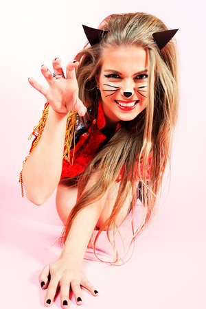 Portrait of a sexy playgirl in pussycat costume alluring over pink background. photo