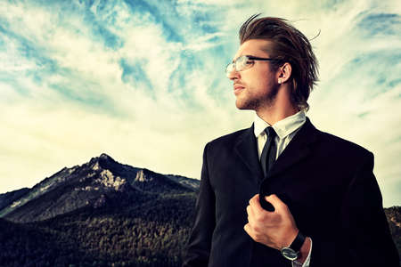 Successful business man standing on a peak of the mountain and purposefully looking away. photo