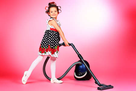 Portrait of a cute little pin-up girl with a vacuum cleaner over pink background.
