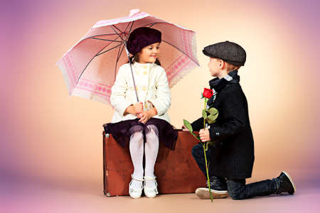 gentleman: Cute little boy is giving a rose to the charming little lady. Retro style. Stock Photo