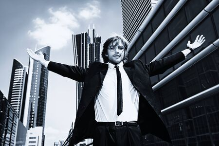 purposeful: Young business man standing in the big city and purposefully looking away.