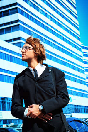 Young business man standing in the big city and purposefully looking away  Stock Photo - 23945089