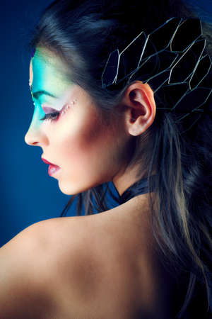 body painting: Portrait of a beautiful young woman with fantasy makeup. Dark background.