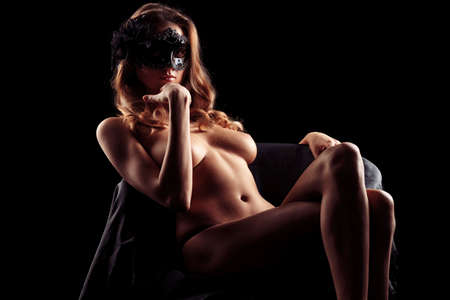 nude art model: Portrait of a beautiful naked woman in carnival mask posing over black background. Stock Photo