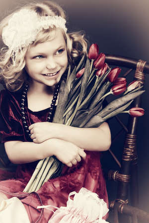 Portrait of a charming little lady with a bouquet of tulips sitting on a bench. Vintage style. photo