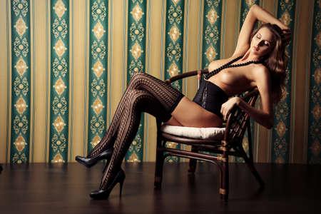 junge frau nackt: Seductive nackte junge Frau in sexuellen Dessous posiert �ber Vintage Hintergrund.