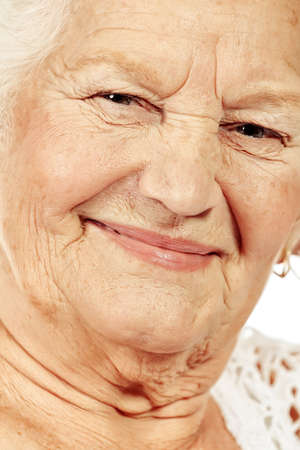 Happy senior woman smiling at the camera. Isolated over white. photo