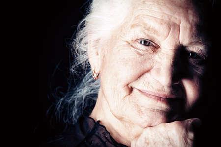 abuela: Retrato de una mujer feliz sonriendo a la c�mara. Sobre fondo negro.