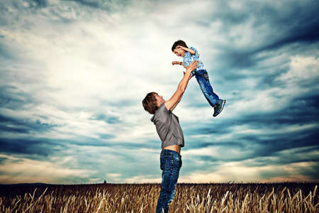 conceptual cute: Happy father playing with his little son in the wheat field over beautiful cloudy sky.