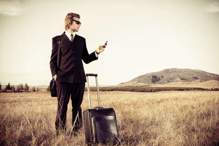 emotional freedom: Handsome business man standing in a field with his suitcase and cell phone. Stock Photo