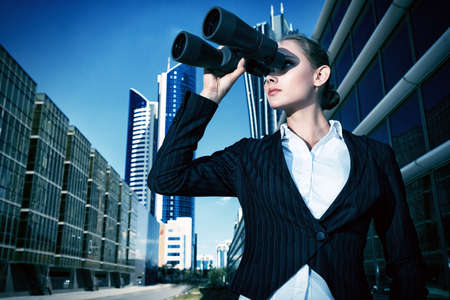 purposeful: Business woman standing in the big city and purposefully looking through the binoculars.  Stock Photo