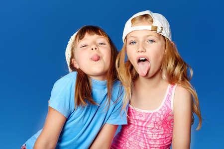 Twee vrolijke meisjes buitenshuis over blauwe hemel.