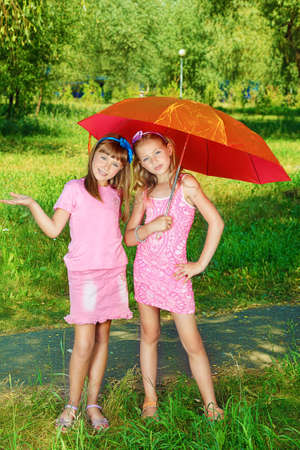 schoolgirls: Two cheerful girls with umbrella at the summer park. Stock Photo
