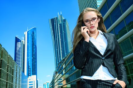 Beautiful businesswoman standing on the street of the big city. Stock Photo - 19165350