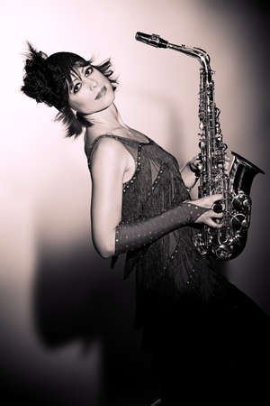 20s  closeup: Professional musician posing with her saxophone at studio.
