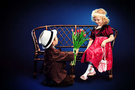 Cute little boy is giving bouquet of tulips to the charming little lady. Retro style. Stock Photo - 19270506