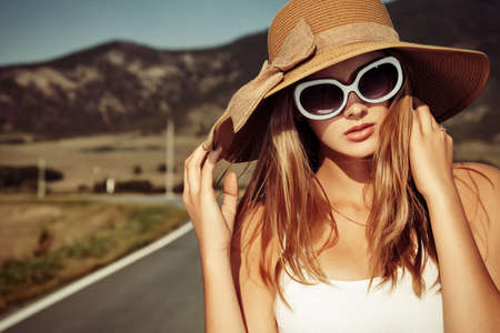 fashionable sunglasses: Beautiful young woman posing on a road over picturesque landscape.