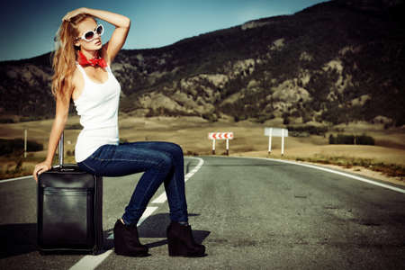fashion girl: Attractive young woman hitchhiking along a road.