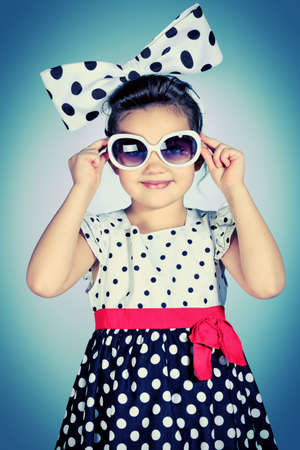 kids dress: Portrait of a cute little pin-up girl in a beautiful dress and big bow.