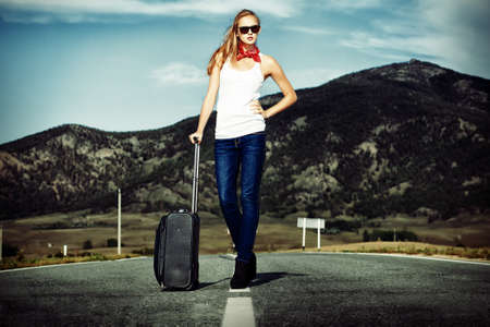 hitchhiking: Attractive young woman hitchhiking along a road.