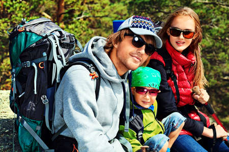 Happy parents hiking with their little son. photo