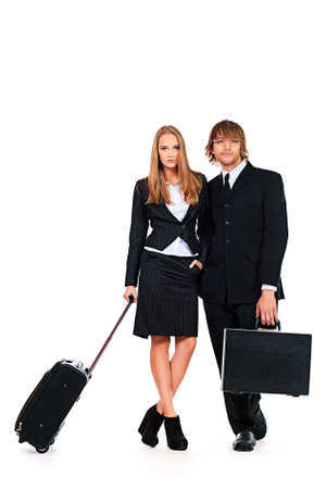 Full length portrait of two successful business people standing with travel bags. Isolated over white. Stock Photo - 19224033