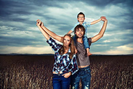 Happy family standing together in the wheat field over beautiful cloudy sky.  photo