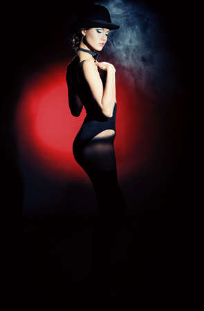 cabaret: Full length portrait of a gorgeous woman in black lingerie. Retro style.  Light and shadow.