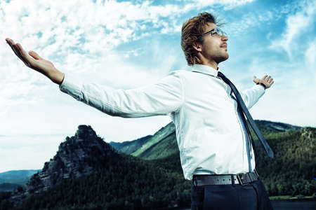 purposeful: Successful business man standing on a peak of the mountain and purposefully looking away.