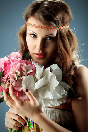 Portrait of a beautiful girl holding a bouquet of flowers. Studio shot. Stock Photo - 19250080