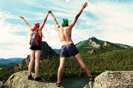 Couple of tourists are standing at the top of a mountain with a feeling of freedom. photo