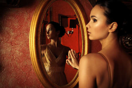 woman mirror: Beautiful young woman in a  luxurious classic interior.