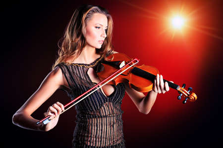 Elegant  young woman playing her violin with expression. photo