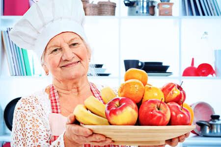 comiendo platano: Principal mujer del cocinero del cocinero de pie, con un plato de frutas en la cocina.