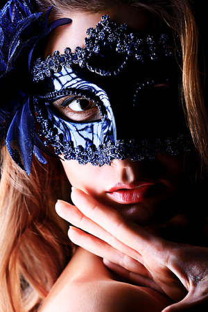 eye ball: Portrait of a beautiful young woman in a carnival mask. Over black background.