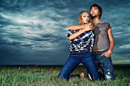 Romantic young couple in casual clothes sitting together in a field on a background of the storm sky.  photo