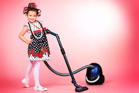 Portrait of a cute little pin-up girl with a vacuum cleaner over pink background. photo
