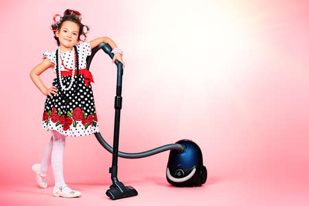 Portrait of a cute little pin-up girl with a vacuum cleaner over pink background. Stock Photo - 19358986