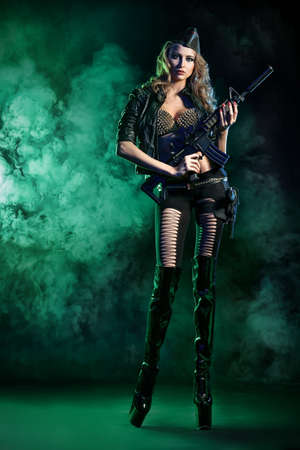 Beautiful sexy woman posing with a gun over dark background. photo