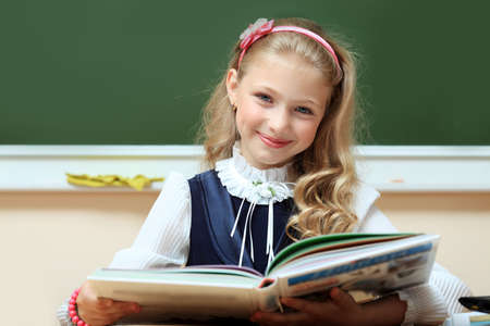 Portrait of a cute schoolgirl in a classroom. photo